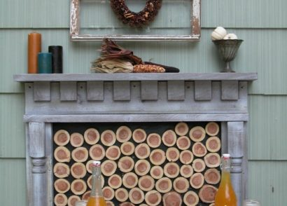 This DIY patio design features a rustic and repurposed touches with a harvest table, faux fireplace, and curtains for privacy. All completed by one couple on a budget by Prodigal Pieces www.prodigalpieces.com #prodigalpieces