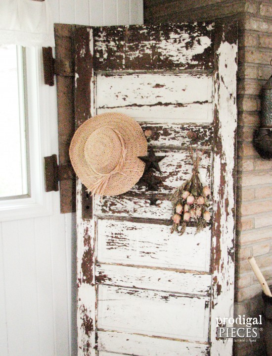 Antique chippy white door becomes functional decor with the addition of barn beam pegs by Prodigal Pieces | prodigalpieces.com