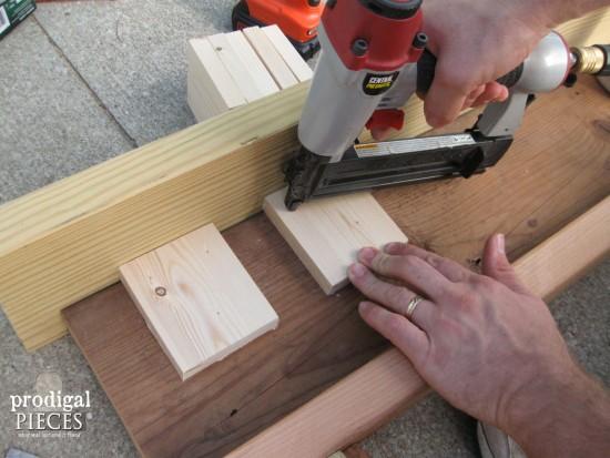 Nailing Dental Blocks on DIY Faux Fireplace | prodigalpieces.com