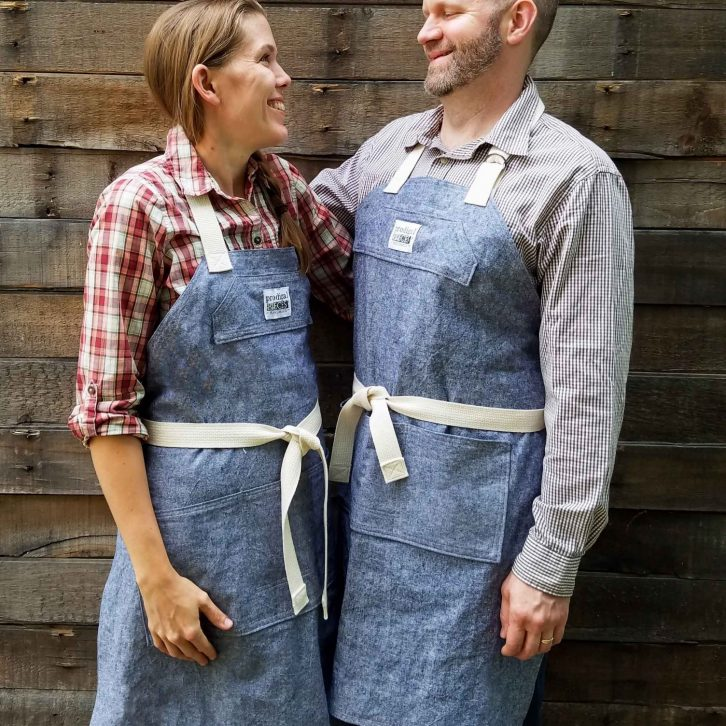 JC & Larissa Haynes in matching linen demi-chef aprons created by Prodigal Pieces | prodigalpieces.com