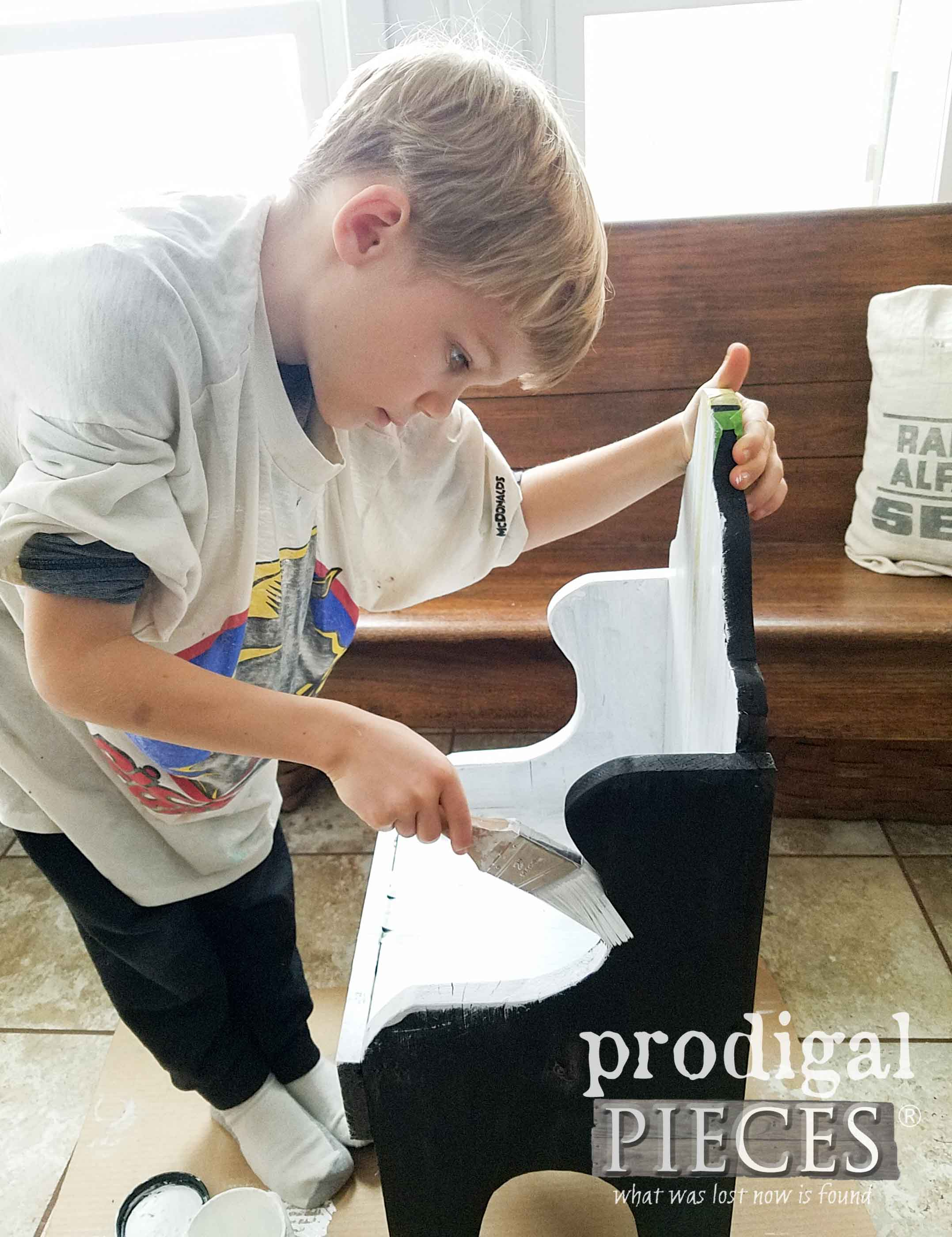 Boy Painting Farmhouse Grain Sack Chair to Learn DIY Skills by Prodigal Pieces | prodigalpieces.com