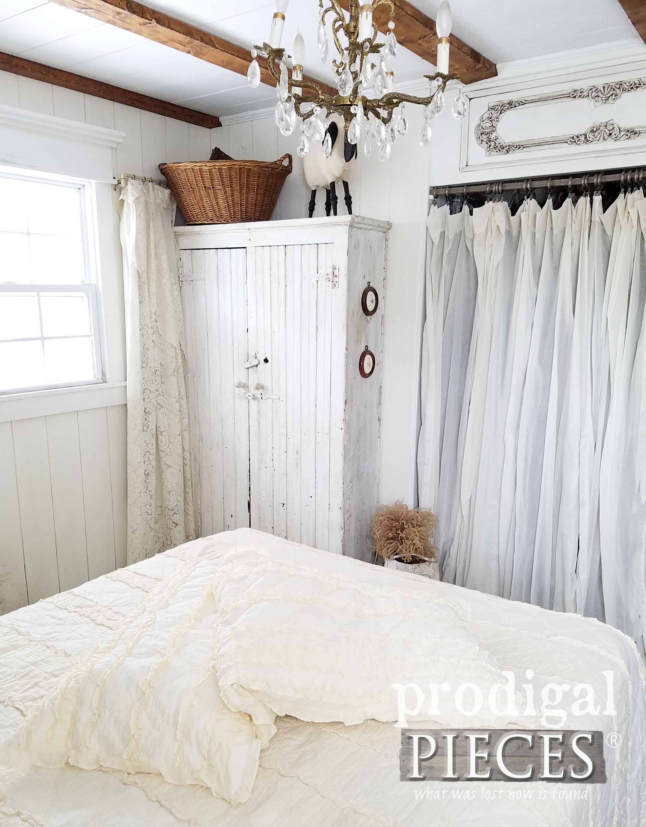 Primitive Chippy White Farmhouse Cupboard with Crystal Chandelier in Farmhouse Master Bedroom by Prodigal Pieces | prodigalpieces.com
