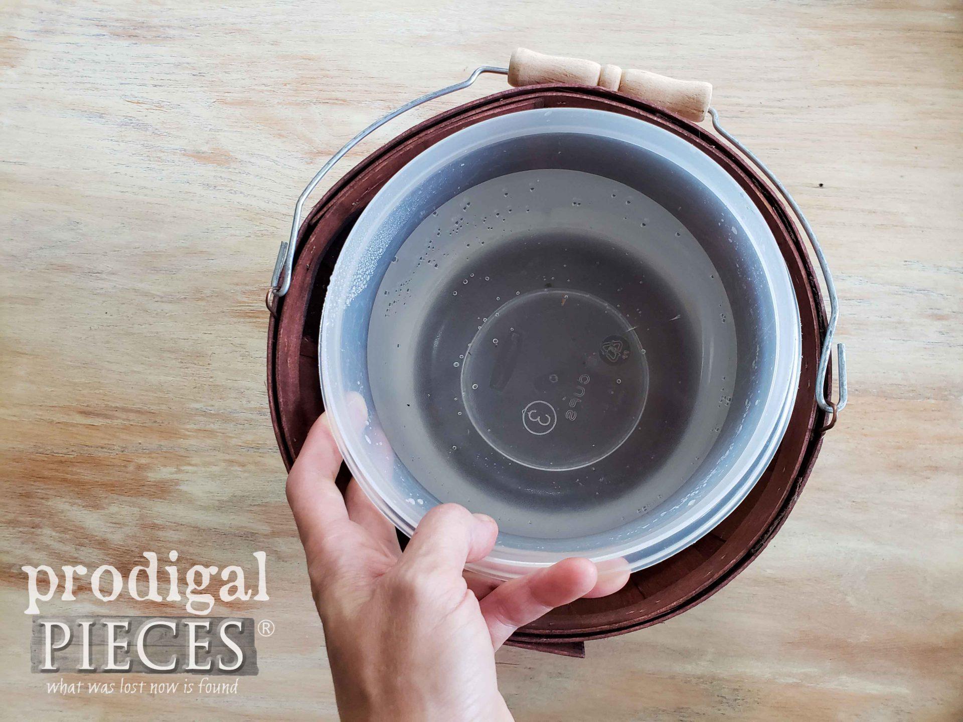 Placing plastic bowl in basket for autumn hydrangea arrangement   prodigalpieces.com