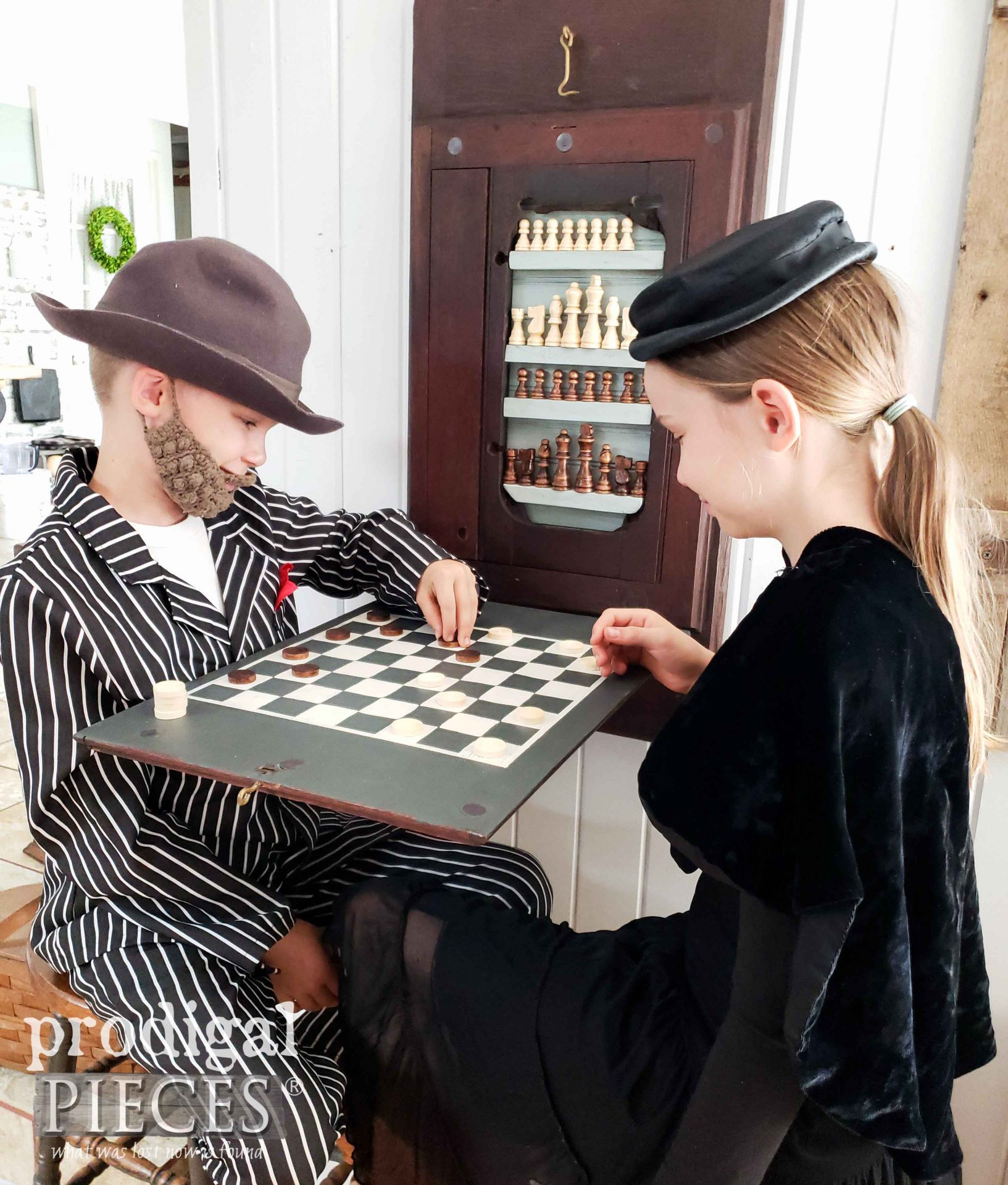 Kids Playing Checkers on Upcycled Sewing Machine Top Game Board created by Larissa of Prodigal Pieces | prodigalpieces.com #prodigalpieces #handmade #home #games #diy #homedecor #farmhouse