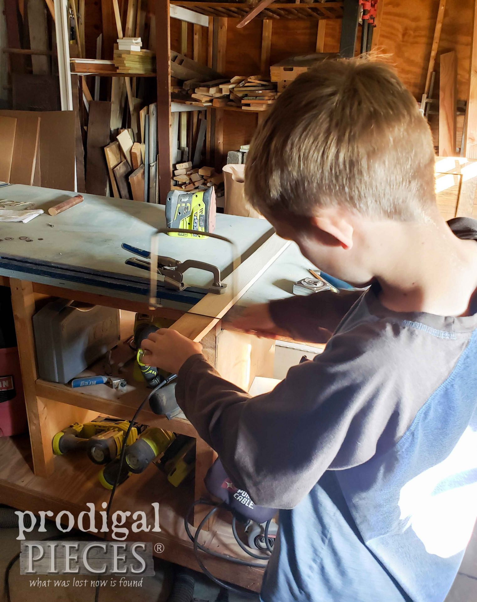 Boy Sawing Scrap Wood to Help with Upcycled Entertainment Center | prodigalpieces.com